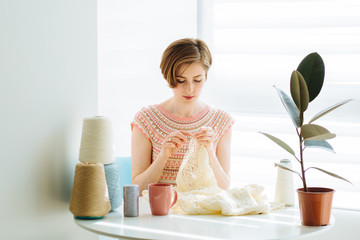 Сraftswoman knitting dress with crochet in cozy workplace at home interior. Female working with tender lace. Business handmade crochet relaxation concept.