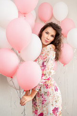 Beautiful young girl in dress with balloons on birthday. Portrait of cute woman with multicolored balloon. Cute brunette girl in the studio with balls filled
