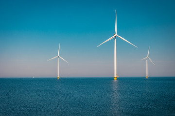 Offshore and Onshore Windmill farm in the ocean ,windmills isolated at sea on a beautiful bright day Netherlands Flevoland Noordoostpolder