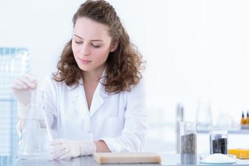 Biotechnologist dissolving sample in solution