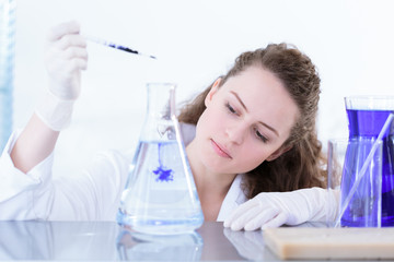 Chemist woman dropping violet oil