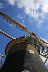 Vertical view of a close up of the top of a windmill against a blue sky