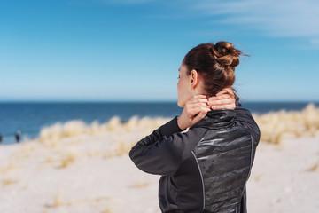 Woman walking on a beach rubbing her neck