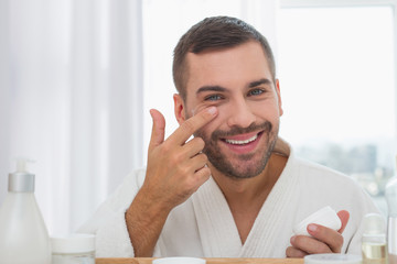 Positive mood. Delighted cheerful man smiling while applying facial cream