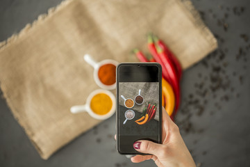 Focus on a woman's hand holding a black phone and using it to take a photo of an arrangement of spices and red and yellow peppers