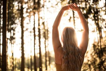 Frau macht Yoga im Wald zum Sonnenuntergang