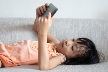 Asian Chinese little girl using tablet lying on the sofa