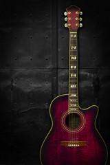 Purple acoustic guitar over dark background