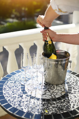 Champagne bottle and four flutes on the table at outdoor