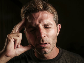 young attractive and sad  man suffering depression and headache with hand on his tempo head in stress looking worried and sick isolated on black