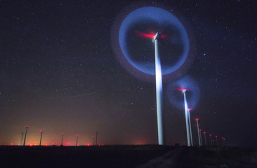 night photo of wind generators and stars with abstract lighting