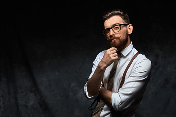 Young stylish hipster with cool hairstyle and beard dressed in white shirt and suspenders is thinking of a new creative idea looking at viewer