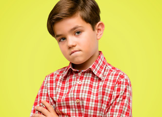 Handsome toddler child with green eyes nervous and scared biting lips looking camera with impatient expression, pensive over yellow background