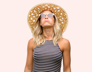 Young woman using sunglasses wearing summer hat with sleepy expression, being overworked and tired