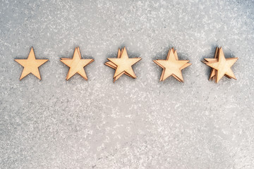 five wooden stars in piles of 1, 2, 3, 4 and 5 pieces on a silver background, top view with copy space