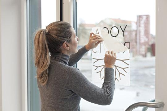 Woman applying company logo film on window