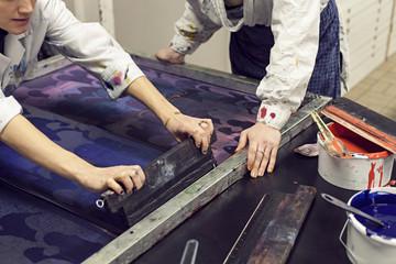 Textile designers screen printing pattern in workshop