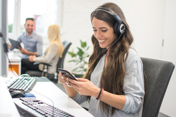 Smiling young woman with headset using mobile phone in office