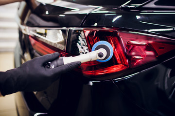 Car polish wax worker hands holding polisher and polish car detailing or valeting concept taillight red car