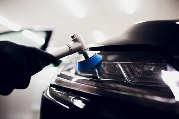 Car polish wax worker hands holding polisher and polish car detailing or valeting concept front white auto headlight