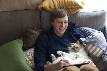 Young man sitting with iPad in sofa with cat sleeping on his belly