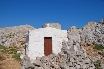 A small chapel and old stone windmill on the high plateau of the Greek island of Halki.