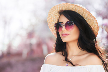 Outdoor close up portrait of young beautiful woman wearing stylish sunglasses, straw boater hat, white cold shoulder blouse. Spring, summer fashion concept. Copy, empty space for text