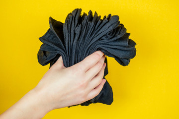 a stack of fresh new black socks in hand on a yellow background