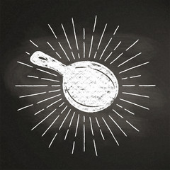 Chalk silhoutte of a pan  with vintage sun rays on blackboard. Good for cooking logotypes, bades, menu design or posters.