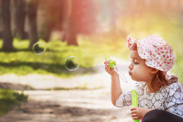 little girl blowing bubbles against nature background. Close-up.
