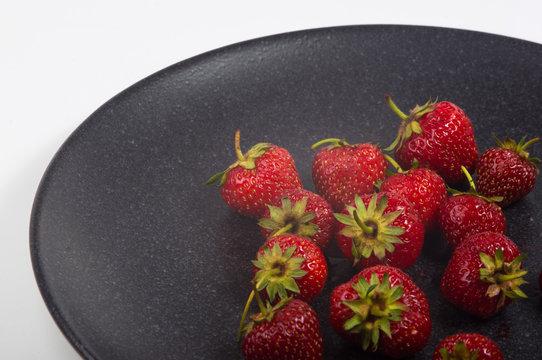 fresh ripe strawberries on black ceramic plate