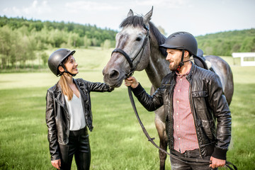 Young couple riders standing near the beautiful horse on the green meadow