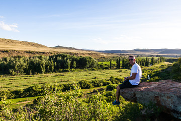 A man sits on an overhanging rock over looking a farmed valley in the Karoo, Nieu Bethesda, South Africa.
