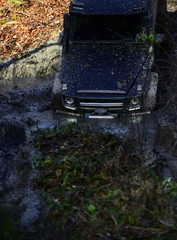 Black crossover driving through dirt with nature on background.