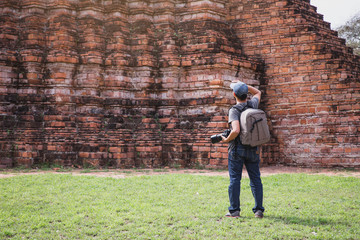 Young Asian traveling backpacker taking photos with camera in Bangkok, Thailand. Male traveler photographing temples at Bangkok.