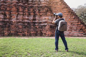 Young Asian traveling backpacker taking photos with camera in Bangkok, Thailand.Male traveler photographing temples at Bangkok.