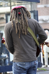 Hombre con rastas tocando la guitarra en la calle.