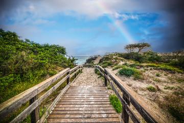 Rainbow over a wooden boardwalk in Alghero coastline at sunset