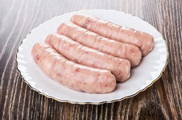 Door stickers Wall Decor With Your Own Photos Raw chicken sausages in white plate on dark table