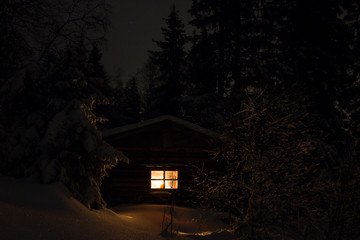 Snowy night with a Christmas candle in a hermit hut