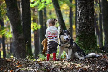 Little girl with dog walking in forest