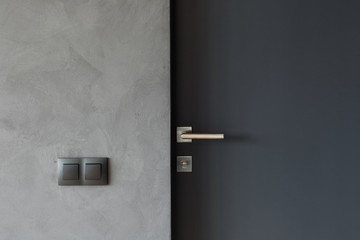 Light switch on the gray textured wall next to the door with metallic handle Wall mural