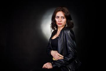 Studio portrait of sexy brunette girl in black leather jacket against black background.