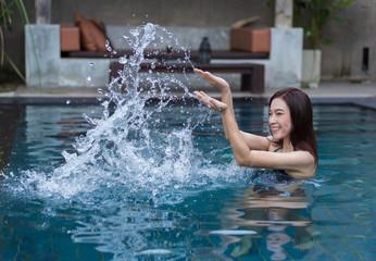 beautiful woman splashing water in swimming pool