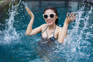 beautiful woman splashing water in swimming pool