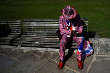 A man wears a Union flag themed suit outside Windsor Castle ahead of Britain's Prince Harry's wedding to Meghan Markle in Windsor