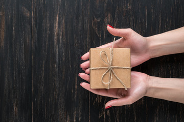 Hand of a young girl opening a gift box on a dark  background.
