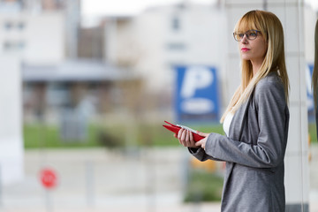 Young attractive woman standing with tablet