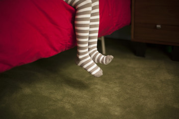 A child's grey and white striped stocking feet sitting on a red bed