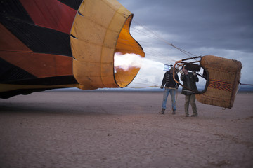 Two men flying a hot air balloon in a dry lake bed